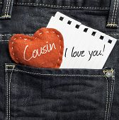 Cousin I love you! written on a peace of paper and a heart on a jeans background