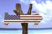 USA wooden sign with a beach on background
