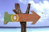 Portugal wooden sign with a beach on background