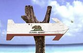 California State wooden sign with a beach on background
