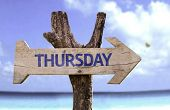 Thursday wooden sign with a beach on background