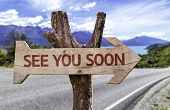 See You Soon wooden sign with a street background