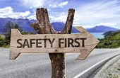 Safety First wooden sign with a street background