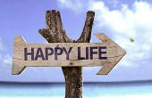 Happy Life wooden sign with a beach on background
