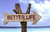 Better Life wooden sign with a beach on background