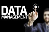 Business man pointing to black board with text: Data Management