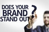 Business man pointing to transparent board with text: Does your Brand Stand Out?