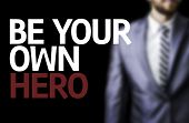 Be your Own Hero written on a board with a business man on background