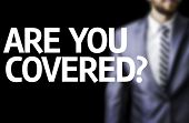 Are you Covered? written on a board with a business man on background