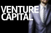 Venture Capital written on a board with a business man on background