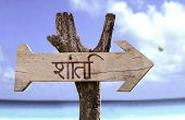 Peace (In Hindi) wooden sign with a beach on background