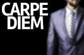 Carpe Diem written on a board with a business man on background