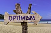 Optimism wooden sign with a beach on background