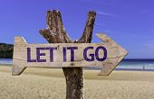 Let It Go wooden sign with a beach on background