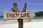 Enjoy Life wooden sign with a beach on background