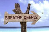 pic of peace-sign  - Breathe Deeply wooden sign with a beach on background - JPG