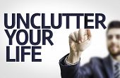 Business man pointing to transparent board with text: Unclutter your Life