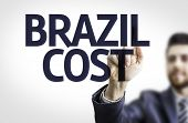 Business man pointing to transparent board with text: Brazil Cost