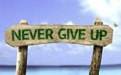 Never Give Up wooden sign with a beach on background