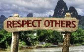 Respect Others wooden sign with a agricultural background