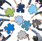 Group of People Holding Jigsaw Puzzle in Photo and Illustration