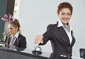 Happy female receptionist worker standing at hotel counter with bell