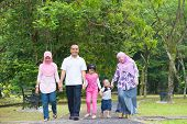 Asian family holding hands walking together on garden path. Happy Southeast Asian outdoor lifestyle.