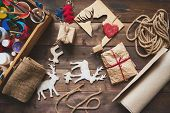 Wrapped Christmas gifts and symbols over wooden background