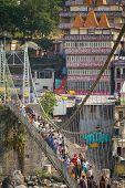 RISHIKESH, INDIA - 2012 NOVEMBER 13: People crossing Lakshman Jhula bridge over Ganges on November 13, 2012 in Rishikesh, India.