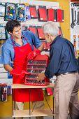 Smiling salesman showing tools to senior man in hardware store