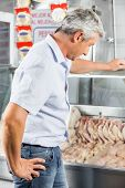 Side view of mature man choosing chicken meat at butchery