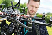 Closeup portrait of male engineer with UAV helicopter in park