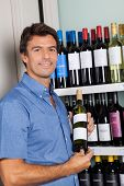 Portrait of mid adult man showing alcohol bottle while standing by shelves at supermarket