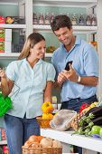 Mid adult couple checking list on mobilephone while shopping in supermarket