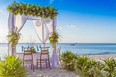 wedding arch and set up on beach, tropical outdoor wedding cabana on beach, wedding table for dinner at sunset
