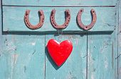 picture of horseshoe  - three old rusty horseshoe luck symbol and red heart on green wooden farm door - JPG