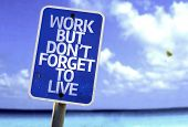 Work But Don't Forget to Live sign with a beach on background