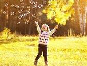 Little Child Having Fun With Bubbles Soap In Sunny Autumn Day