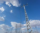 Wide view of electric tower group over blue sky and clouds