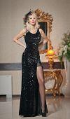 Young beautiful luxurious woman in long elegant black dress. Beautiful young blonde woman