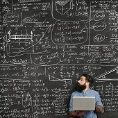 Bearded Man With Laptop Looking At Chalkboard With Formulas