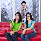 Asian Teenager Drinking Champagne On Sofa