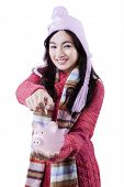 foto of japanese coin  - Portrait of a beautiful girl wearing winter clothes holding a piggybank and put a coin - JPG
