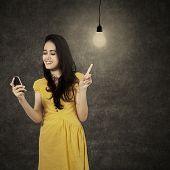 Young Woman With Cellphone Under Lightbulb