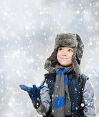 foto of headgear  - Winter fur hat clothing boy with outstretched hand and looking snow falling
