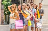 pic of overspending  - Group of friends holding shopping bags outdoors - JPG