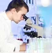 stock photo of microscope slide  - Young male researcher looking at the microscope slide in the life science laboratory. Forensics, microbiology, biochemistry, genetics, oncology...