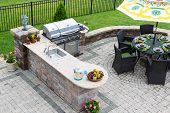 stock photo of plant pot  - High angle view of a stylish outdoor kitchen gas barbecue and dining table set for entertaining guests with formal place settings and flowers on a paved patio - JPG