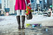 picture of wet feet  - Woman wearing rain boots stay into a puddle - JPG