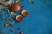 pic of teapot  - teapot with two cups on blue wooden table focus on the teapot - JPG